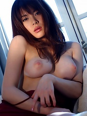 Japanese girl in red lingerie poses on the couch and slowly strips out of her clothes and lies back to show off her milky white tit