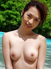 Sexy Japanese girl poses in her colorful bikini at the beach and gets her nice tits and ass all wet.